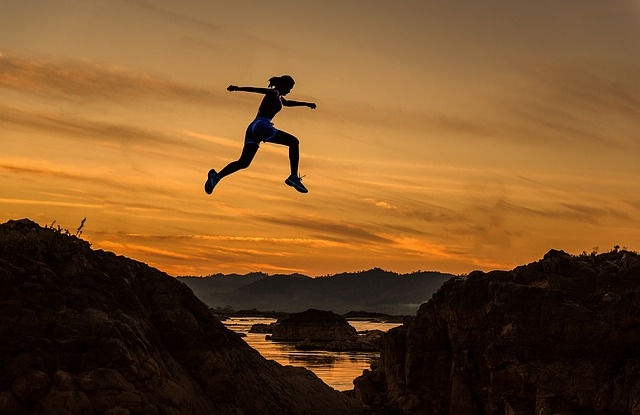 leap of faith woman jumping across a valley manifesting your dream life