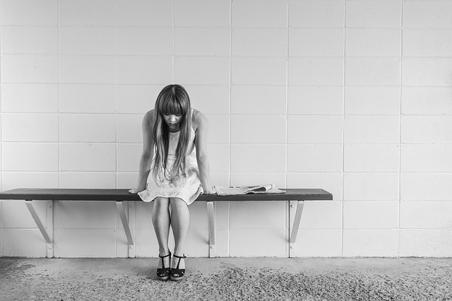 how to handle stress girl sitting on a bench with head down