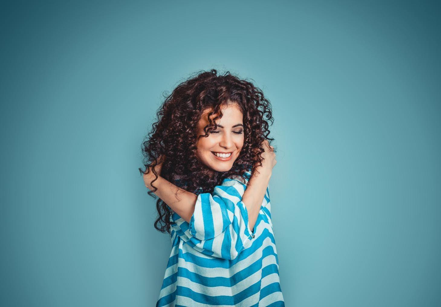 self-confidence booster woman hugging herself against blue wall