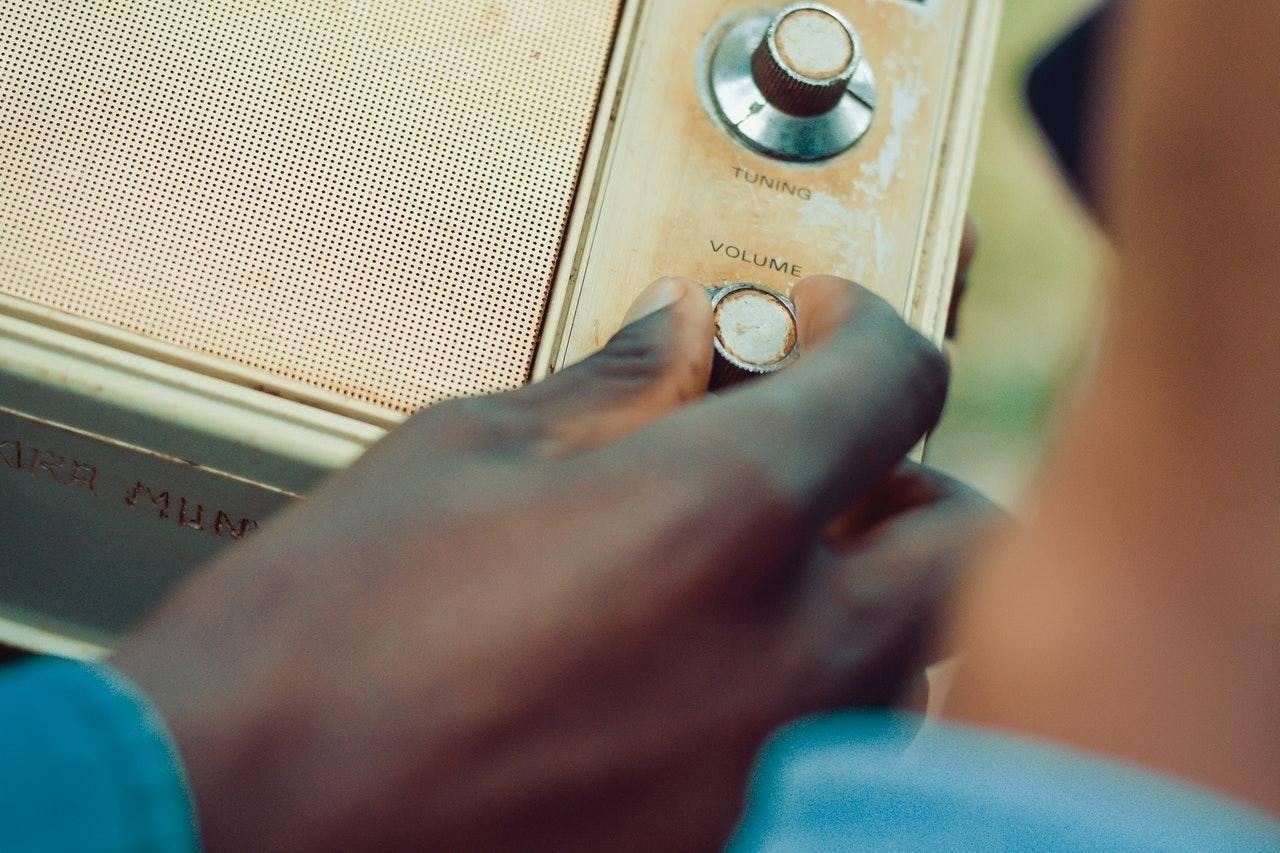 hand on the knob of an old fashion radio