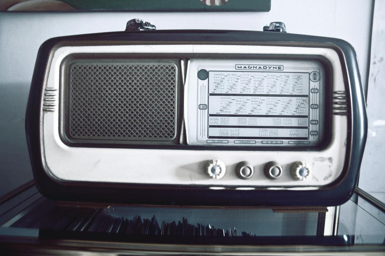 an old-fashioned radio on a glass table ride the airwaves