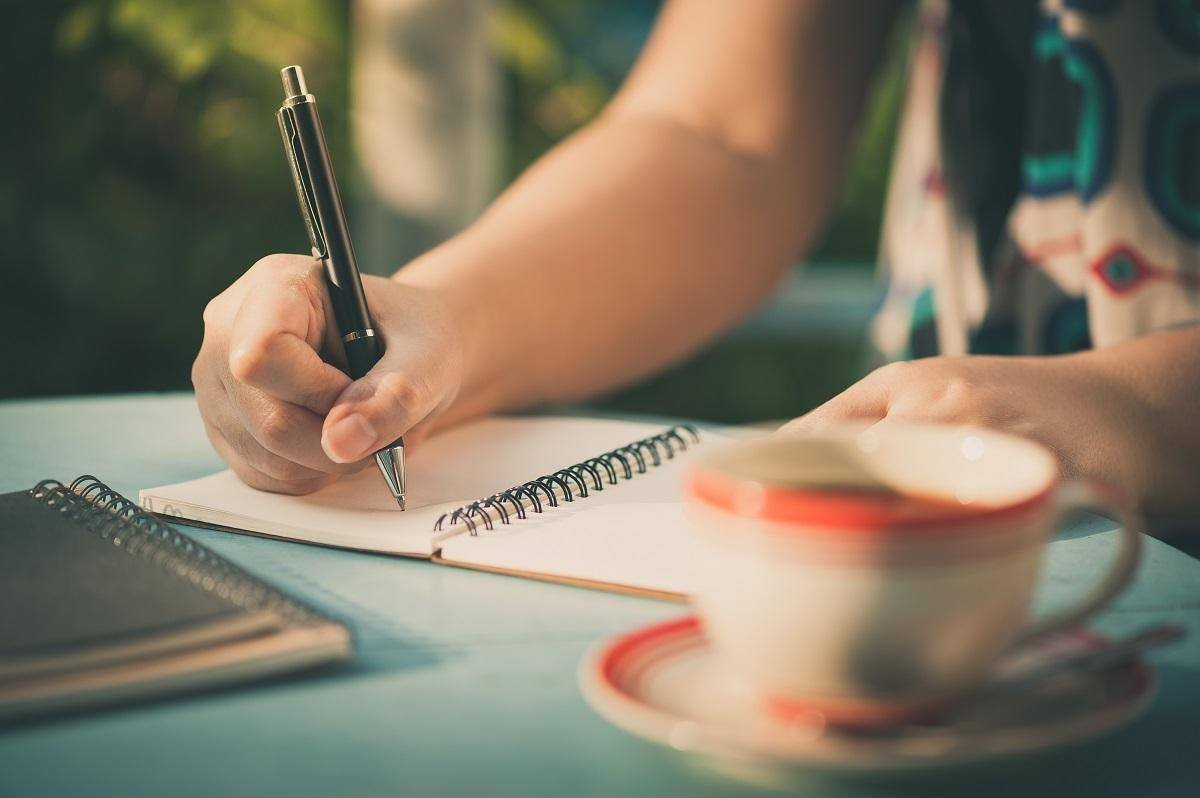 woman writing in notebook beside cup of coffee