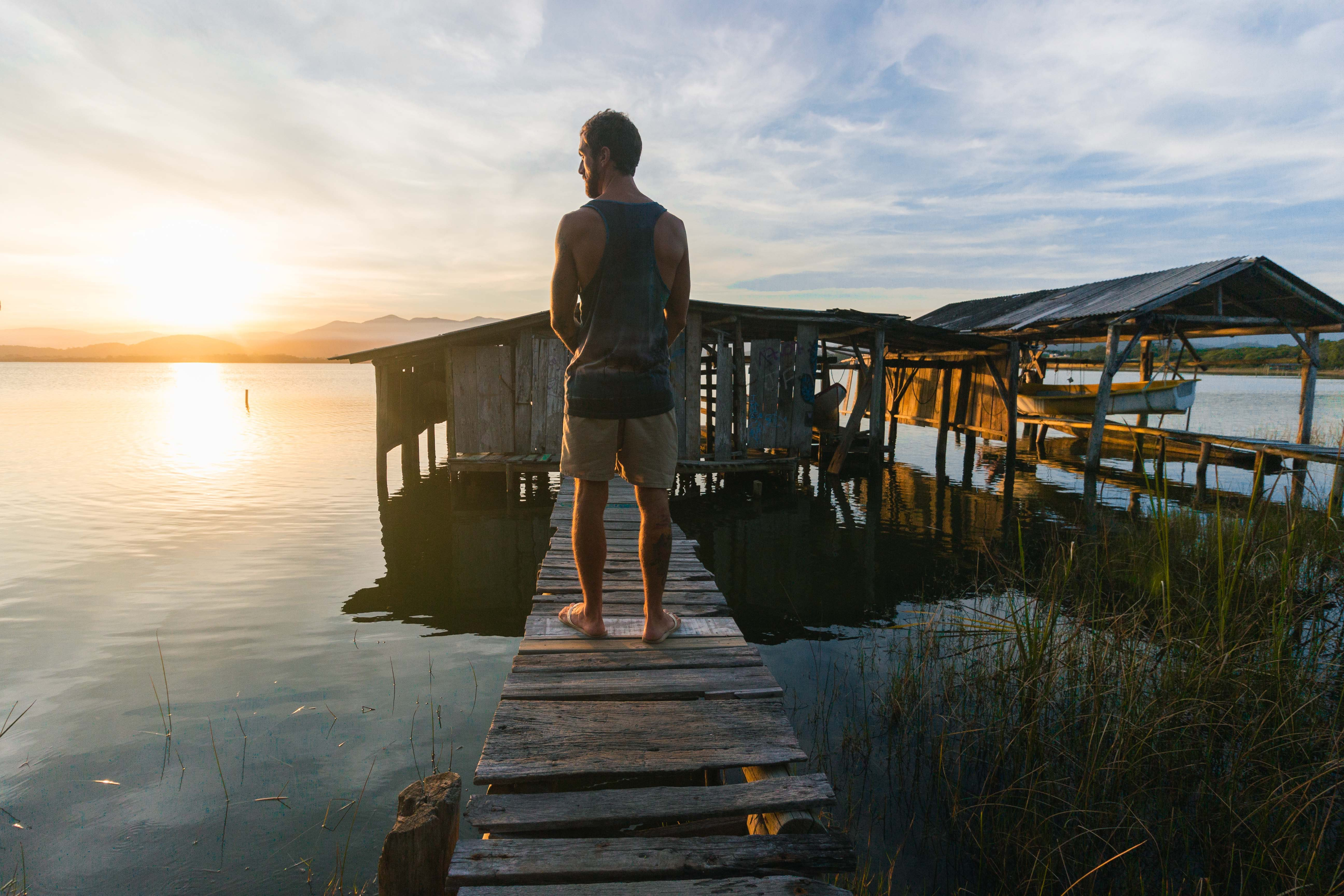 man on a pier at sunset looking meditatively how do i become successful