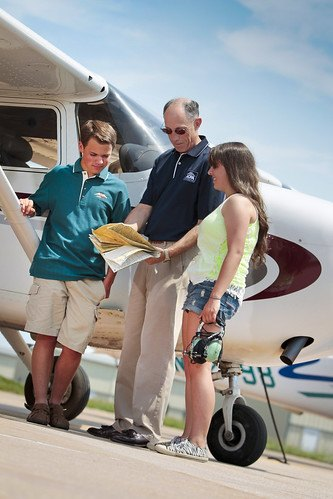 father son daughter at pilot training standing beside airplane