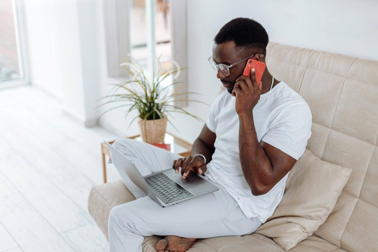 man on sofa using cell phone