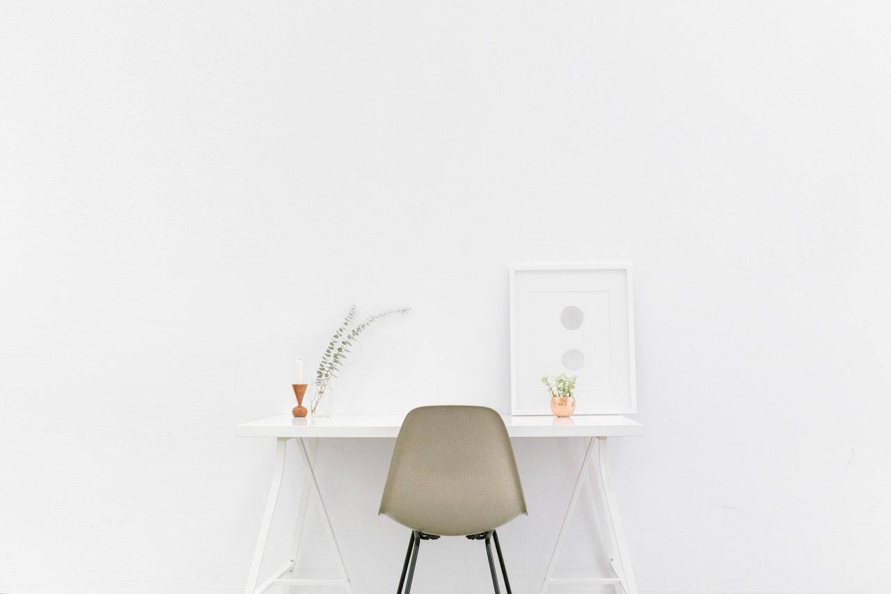 white table against white wall with beige chair under itwhite picture frame benefits of minimalism